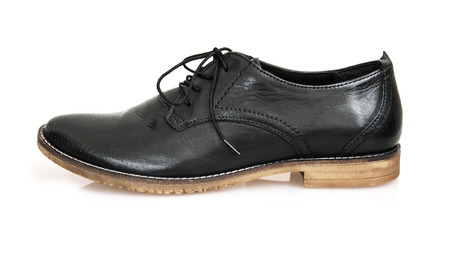 One new black leather shoe on the white background. photo