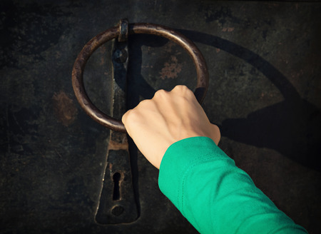 woman's hand: Womans hand knocking on the old door with knocker. Stock Photo