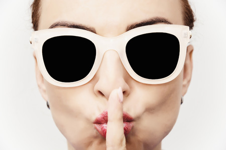 stylish: Young caucasian glamour woman with stylish sunglasses and finger to her mouth. Beauty and fashion.