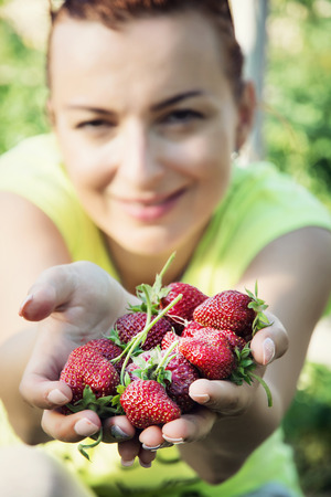caucasian woman: Young caucasian woman with a handful of fresh strawberries. Summer garden.