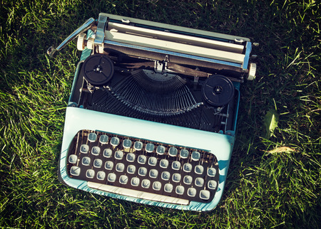 Old typewriter on the grass. Retro style.