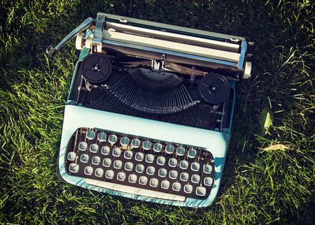 Old typewriter on the grass. Retro style.