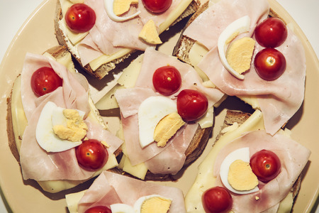 multi grain sandwich: Tasty sandwiches with egg, cheese, ham and cherry tomatoes. Food and drink theme.