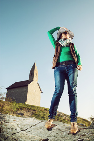 archangel: Young woman posing with stylish hat. Cowboy style. Old romanesque church Archangel Michael in Slovak republic.
