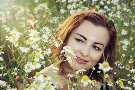 summer time: Young caucasian brunette woman in daisy meadow. Summer time.