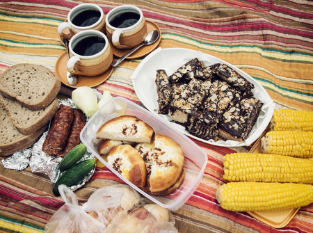 picknick: Picnic menu with deep dish pie with almonds and chocolate, curd cakes, bread, meat sausage, onion, corn and cups of coffee on the retro blanket.