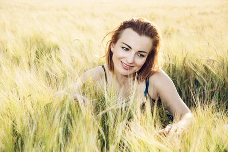 smoothing: Woman in love is smoothing the wheat cobs in the field. Stock Photo