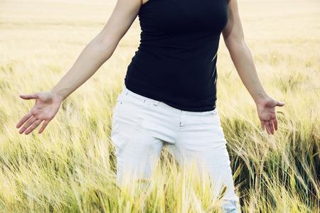 expresion corporal: La mujer se está alisando las mazorcas de trigo en el campo. Parte del cuerpo.