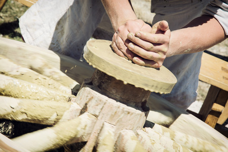 alfarero: El alfarero trabaja manualmente en el torno de alfarero.