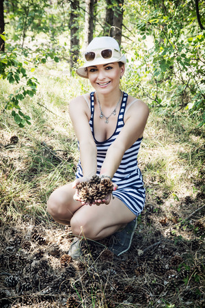 caucasian woman: Smiling caucasian woman enjoying the pine cones in the forest by summer. Natural beauty. Stock Photo