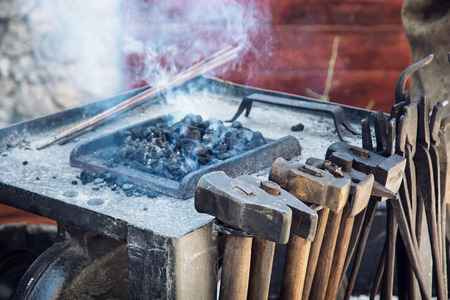 manufactory: Old blacksmith tools in the historical manufactory. Burning embers. Stock Photo