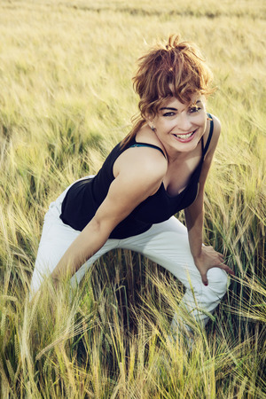 extravagant: Young caucasian woman with extravagant hairstyle in wheat field by sunset. Beauty and fashion.