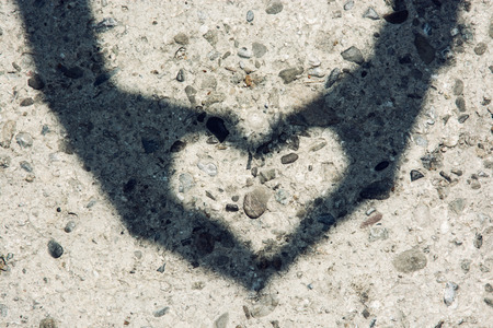 Young woman makes heart shadow with her hands at the stone paving.