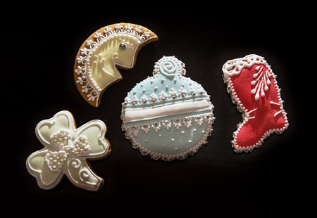 jackboot: Gingerbread cookies on the dark background. Moon, boot, trefoil and bauble. Christmas theme. Stock Photo