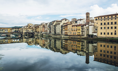 mirroring: Ponte Vecchio and historical buildings are mirroring in the river Arno, Florence, Tuscany, Italy.