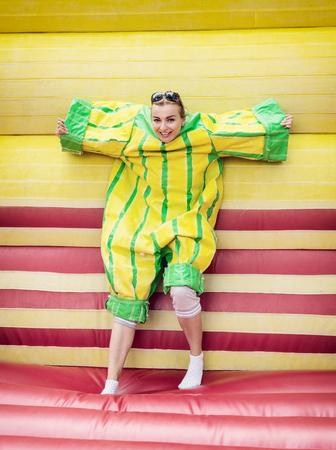 velcro: Young woman in plastic dress in a bouncy castle imitates a fly on velcro wall. Inflatable attraction. Stock Photo