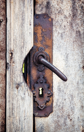 door knob: Rusty door knob on the wooden doors.