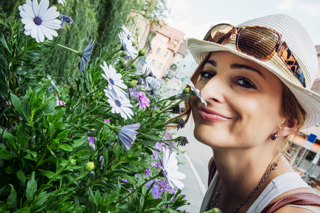sniff: Young caucasian woman sniff beautiful flowers in the city park. Schwabach, Germany.