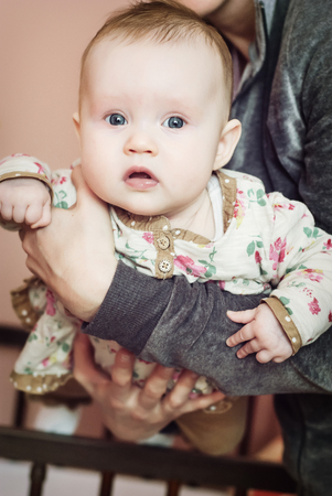 babycare: Cute baby girl in mothers arms. Babycare theme.