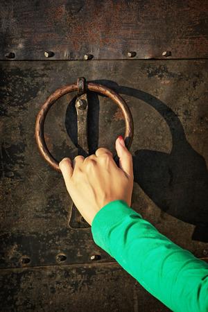 Vintage knocker door with woman's hand.