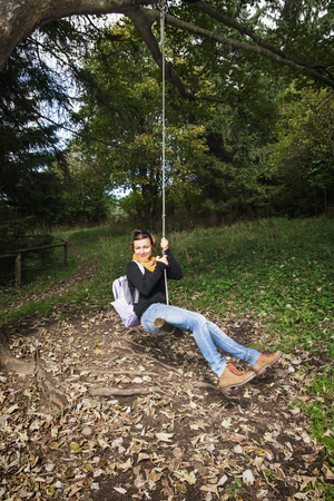 outdoor activity: Happy young woman swing on the rope. Outdoor activity.