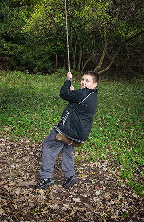 outdoor activity: Young boy swing on the rope. Outdoor activity.