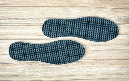 breathable: Shoe insoles on the wooden background.