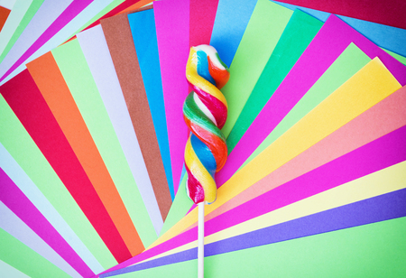 mellowness: Colorful twisted sweet lollipop with brightly colored papers. Rainbow theme. Funny photo.