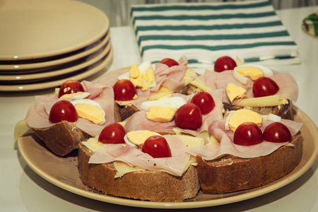 multi grain sandwich: Sandwiches with egg, cheese, ham and cherry tomatoes. Food and drink theme. Toned photo.