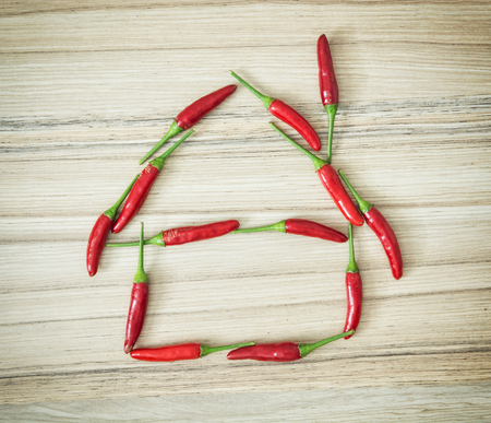 vibrant cottage: Chili peppers in the house shape on the wooden background.