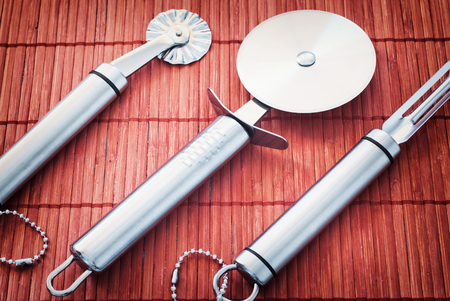 stainless steel kitchen: Set of new stainless steel kitchen tools on the red bamboo background.