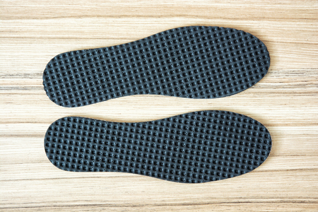 breathable: New shoe insoles on the wooden background. Archivio Fotografico
