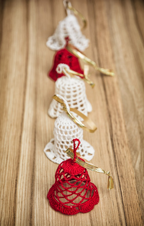 christmas bells: Red and white crochet christmas bells on the wooden background.