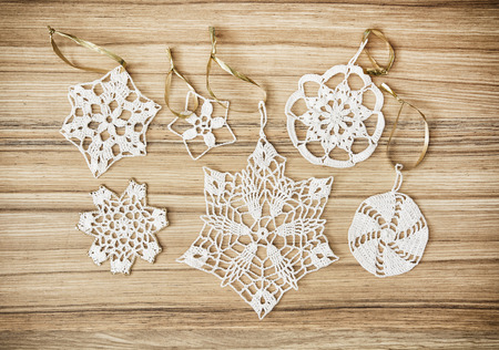 navidad: White crochet christmas decorations on the wooden background.