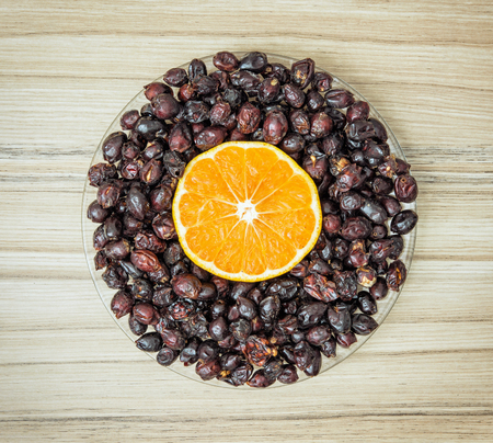 sliced orange: Dried rosehips and sliced orange arranged in the bowl on the wooden background. Healthy lifestyle.