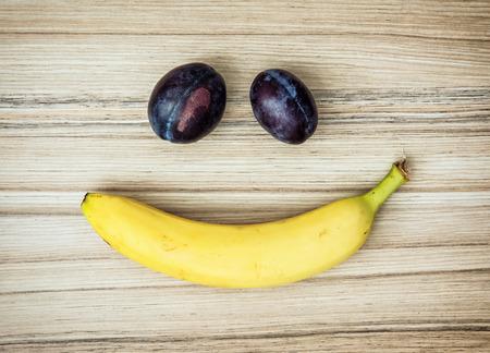 carita feliz: cara sonriente del pl�tano y ciruelas. tema de la fruta. Estilo de vida saludable.