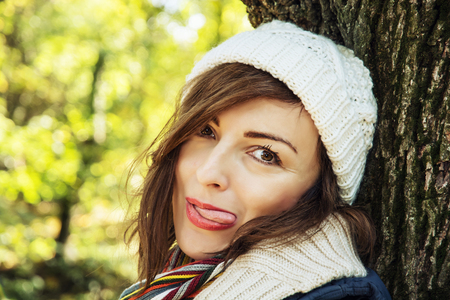face in tree bark: Young crazy positive woman posing in autumn park. Beauty, fashion and nature. Stock Photo