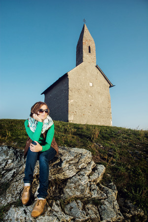 michael the archangel: Young caucasian woman is sitting in front of the Archangel Michael church, Slovakia.