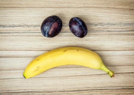 cara triste: Cara triste del plátano y ciruelas. Tema de la fruta. Estilo de vida saludable. Foto de archivo