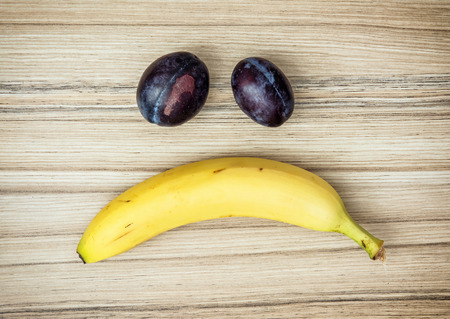 sad face: Sad face of banana and plums. Fruit theme. Healthy lifestyle. Stock Photo