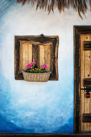 blue wall: Wooden window with flowers, blue wall and door with padlock. Retro style. Rural scene.