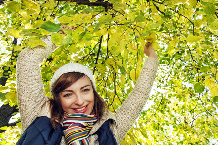 beech tree: Beautiful smiling brunette posing under the beech tree in autumn nature. Beauty and fashion. Stock Photo