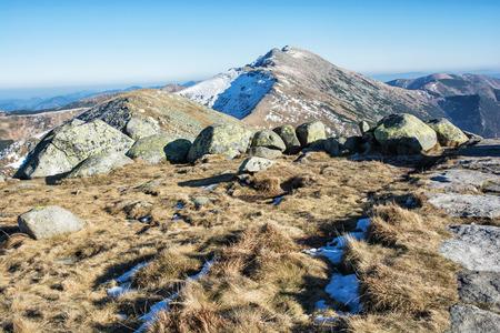mountainy: Dumbier is highest peak of slovak mountains Low Tatras, Slovakia. Hiking theme. Seasonal scene. Big stones, dry grass and snow.