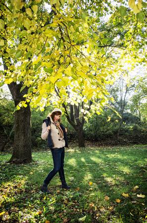 beech tree beech: Beautiful young positive woman posing under the beech tree in autumn nature. Seasonal fashion. Stock Photo