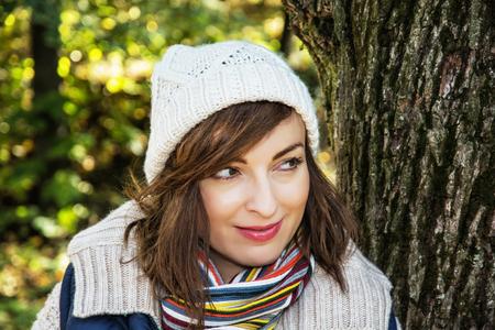 face in tree bark: Young positive caucasian woman posing in autumn park. Seasonal fashion. Female portrait.
