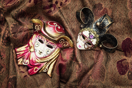 masquerade masks: Two masquerade carnival masks on the fabric background. Beauty and fashion.