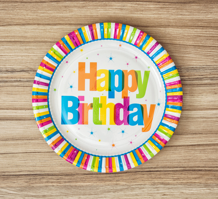 paper plates: Paper plates designed for birthday party on the wooden background. Holidays theme. Stock Photo