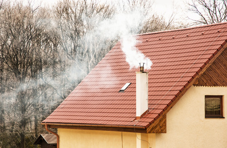 Smoking chimney on the red roof. Seasonal scene. Rural house.