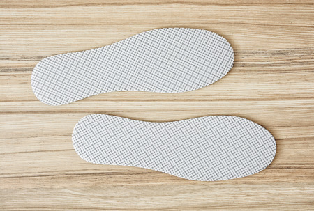 breathable: New white shoe insoles on the wooden background.