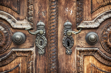 crank: Old hand-carved wooden pattern on the door with forged crank. Stock Photo